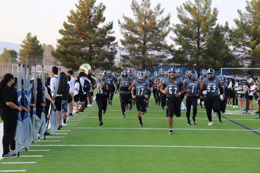 The Desert Pines Varsity Football team runs onto the field for their game against Centennial High School on September 24, 2001.